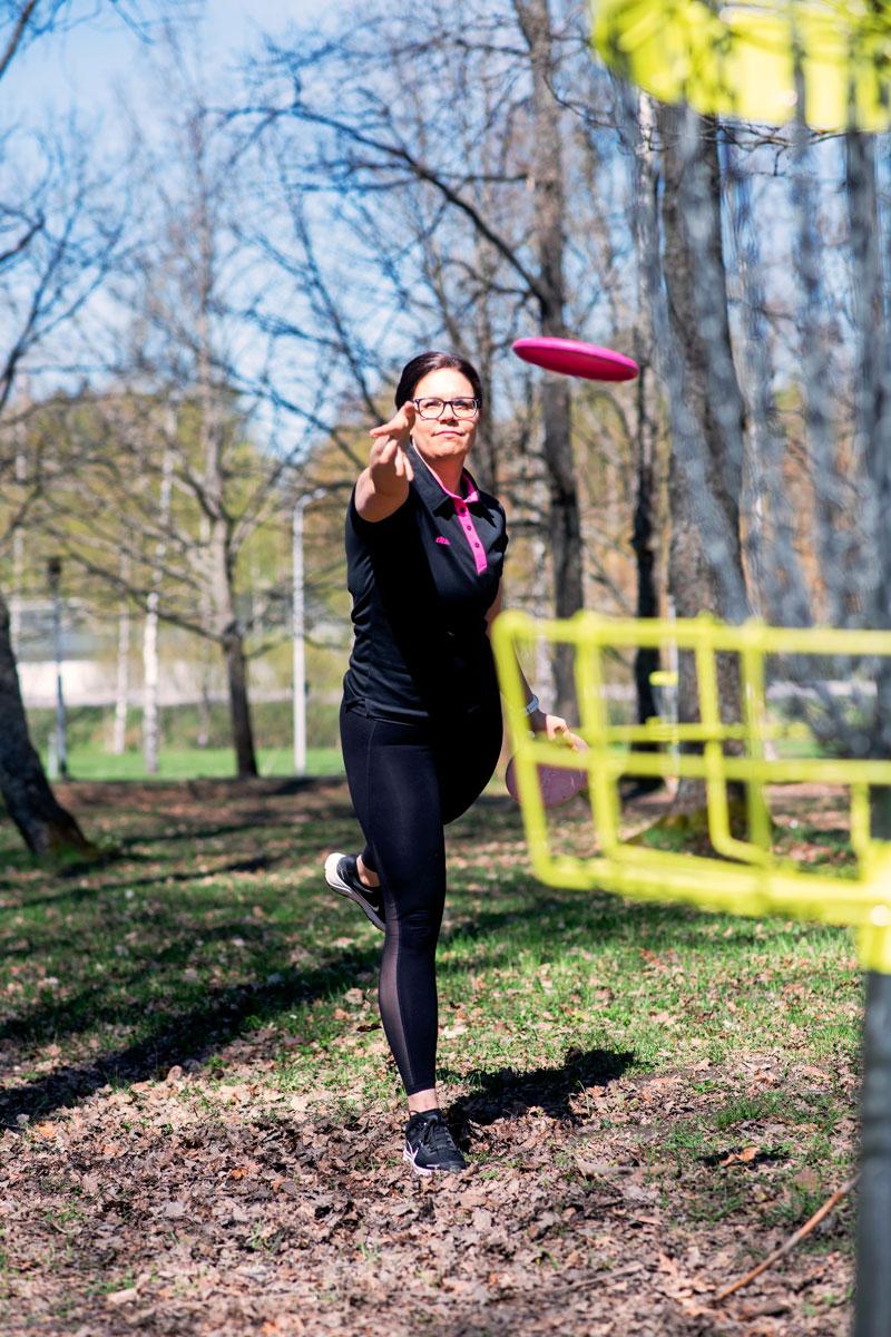 Sanna Särkelä heittää frisbeegolf-kiekkoa.