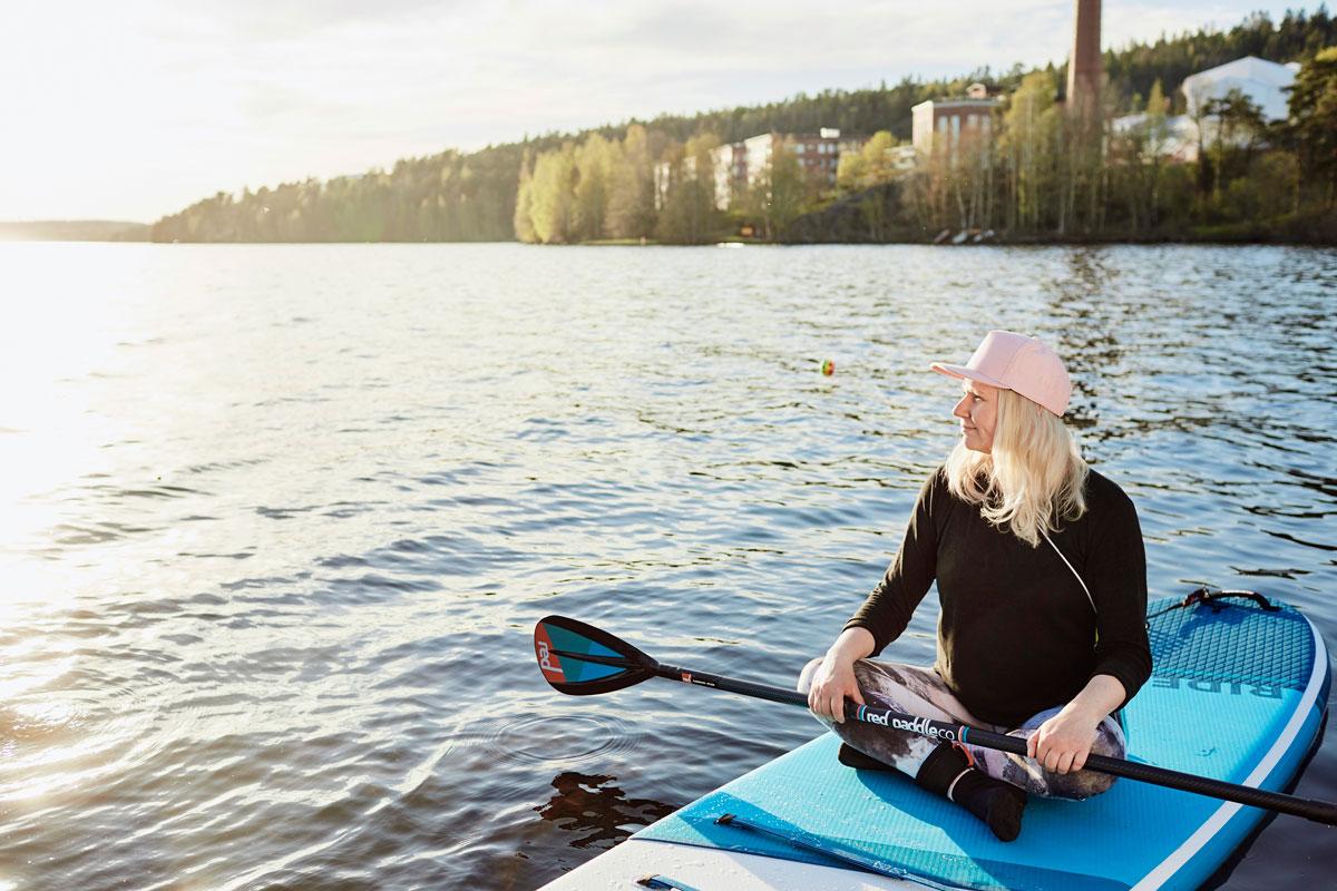 Sanna Juutilainen istuu sup-laudalla vedessä.