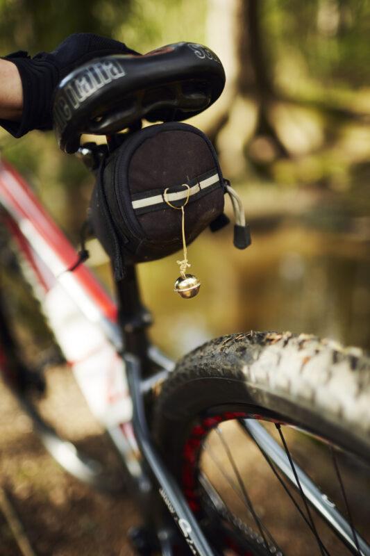 Lähikuva pyörän satulaan kiinnitetystä karhukellosta.