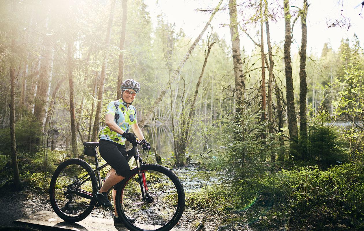 Tuija Aali pyöränsä selässä metsässä.