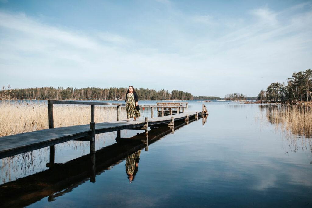 Kaisa Pöyhiä kävelee puista laituria pitkin järvimaisema taustallaan.