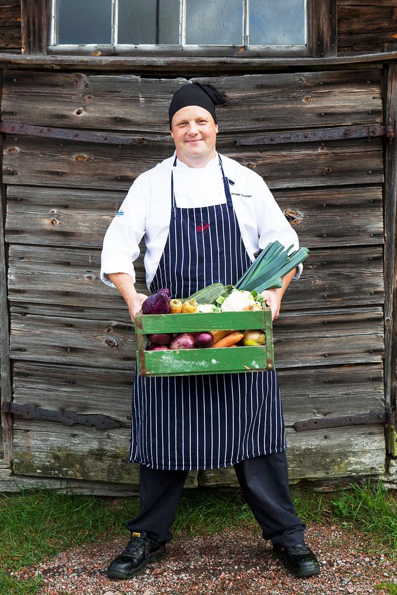 Michael Björklund seisoo vihanneslaatikko käsissään seinän edessä.