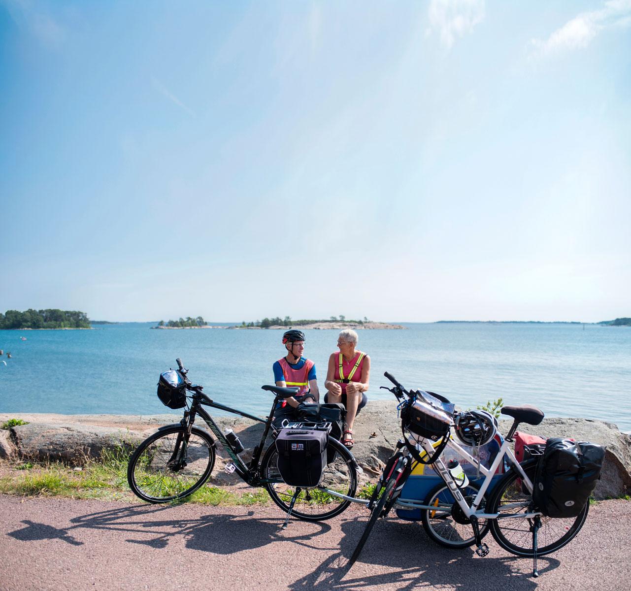 Kaksi ihmistä istuu kallioilla meren äärellä edessään pyörät. Ahvenanmaa on erinomainen pyöräilypaikka.