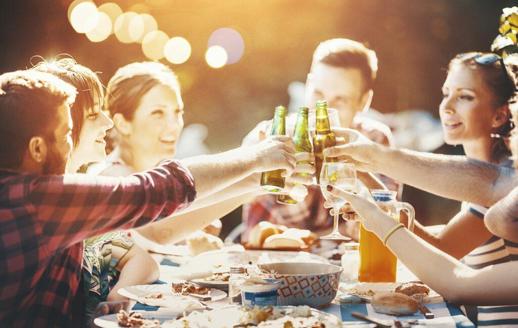 Ihmiset kilistävät pulloja ja laseja pöydän ääressä.