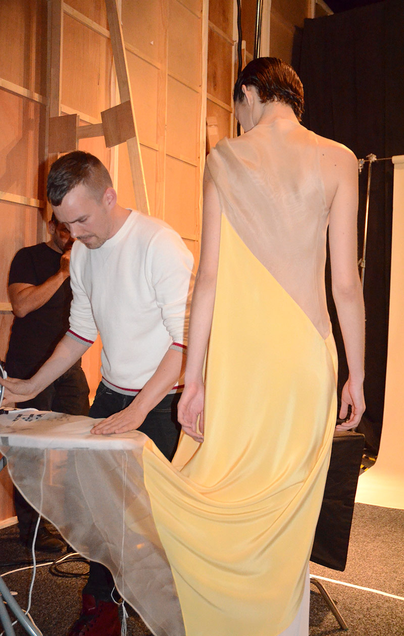 Teemu silittää iltapuvun helmaa muotinäytöksen takahuoneessa Sydneyssä.