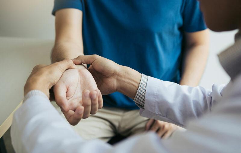 Lääkäri pitelee ja tutkii potilaan rannetta.
