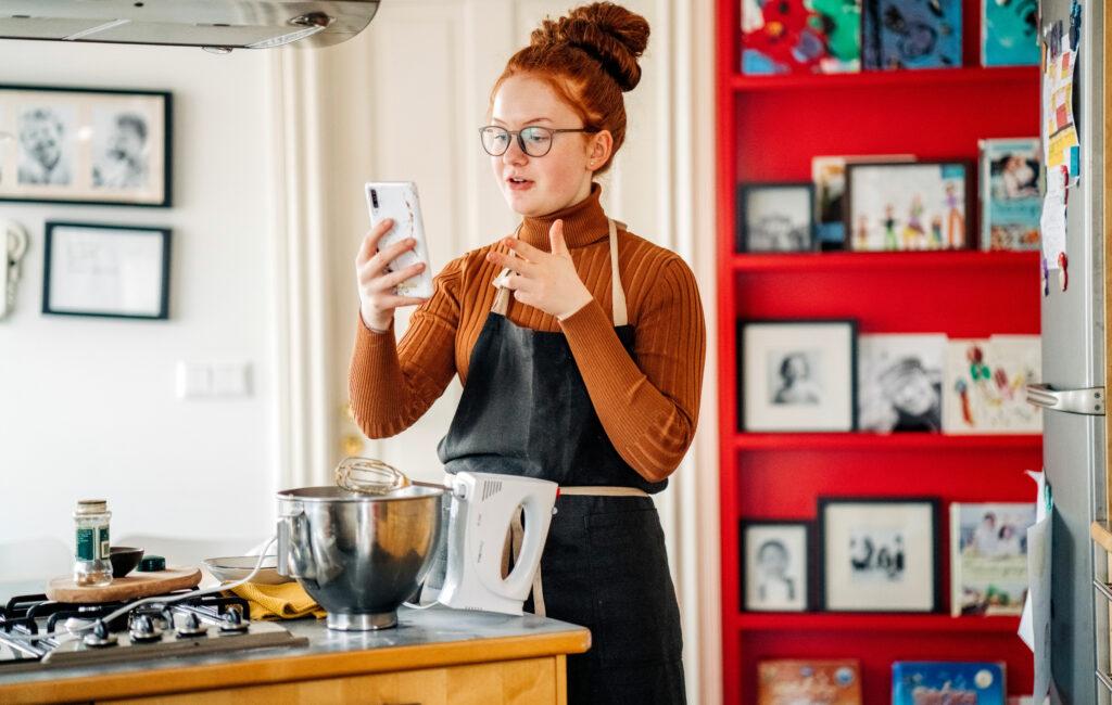 Kotileipuri katsoo puhelintaan leivonnan lomassa.