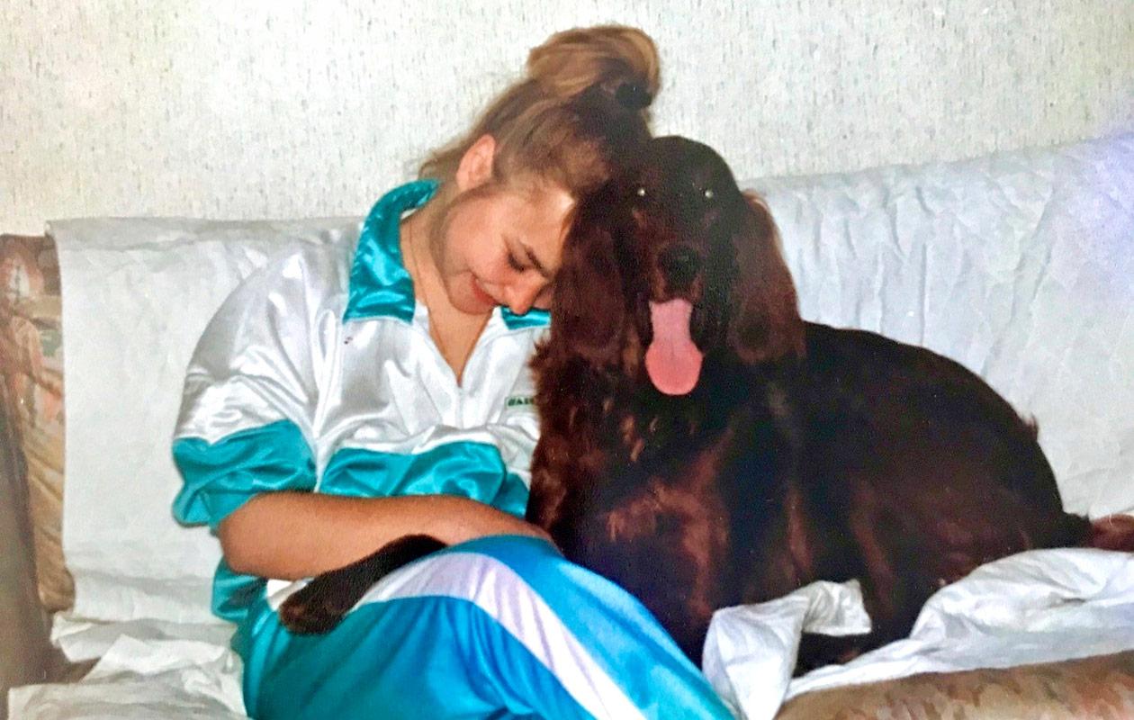 Sonja istuu koira vieressään ja nojaa päätään koiran päähän.