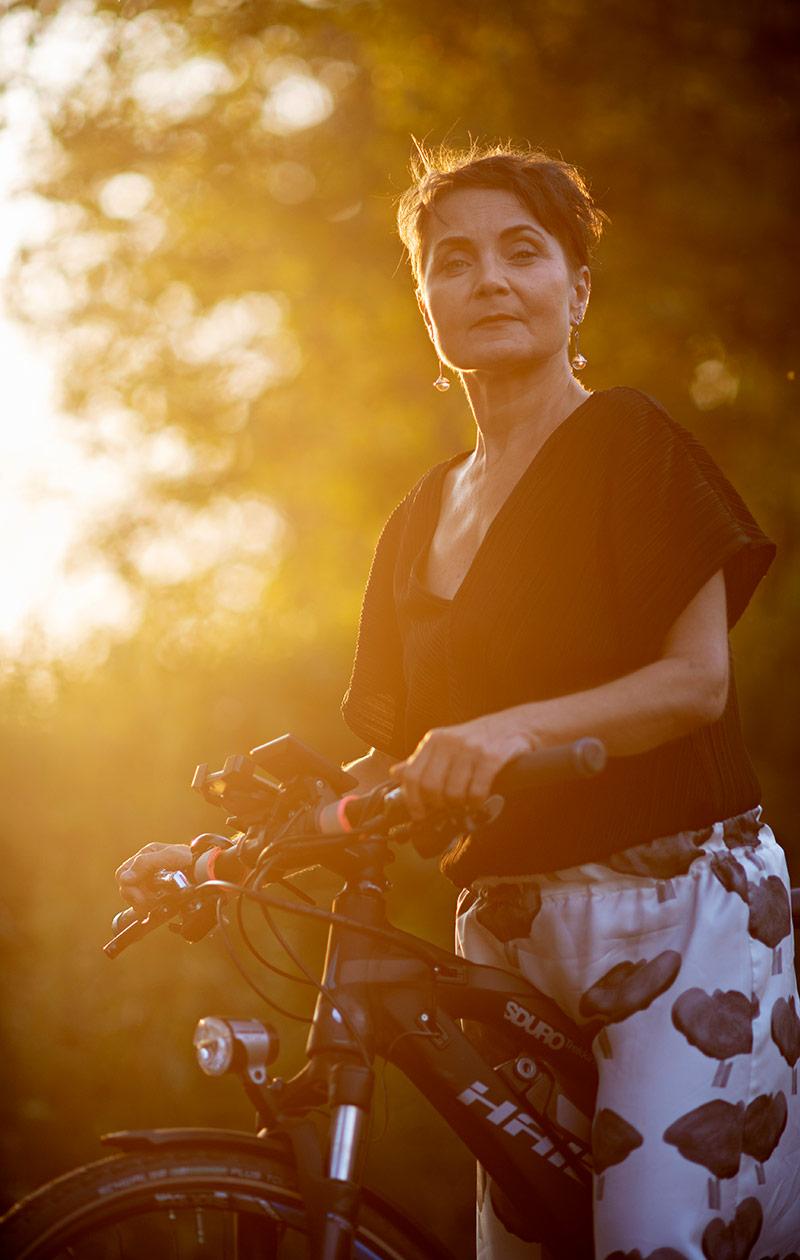 Sonja katsoo kameraan ja pitää pyöränsä ohjaustangosta kiinni.