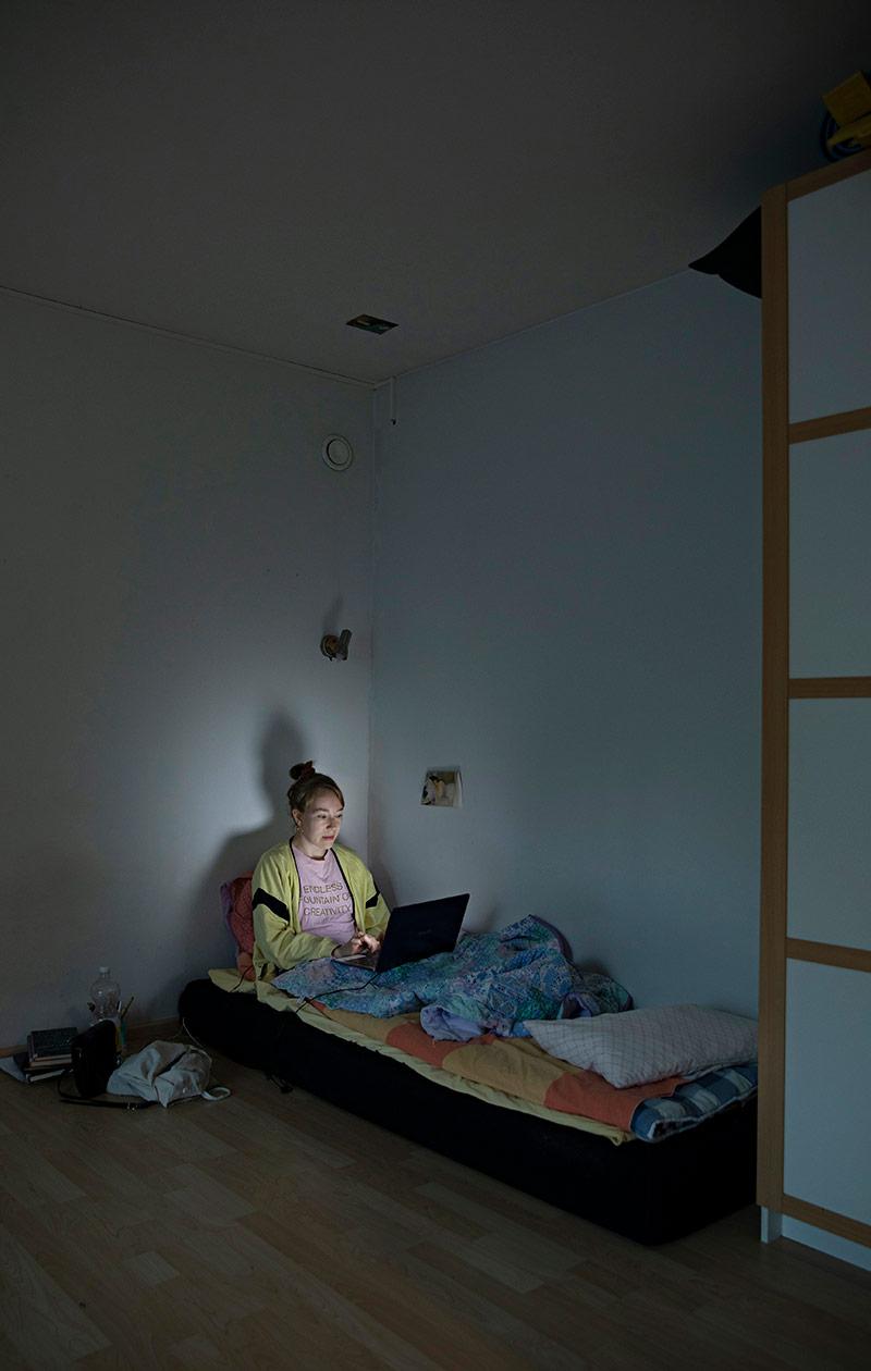 Hanna Storm istuu sängyllä ja tietokoneen näyttö valaisee hänen kasvonsa.
