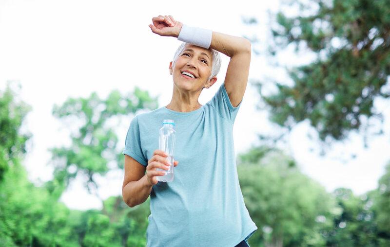Iäkkäämpi nainen pyyhkii urheilun jälkeen hikistä otsaansa. Kädessä vesipullo.