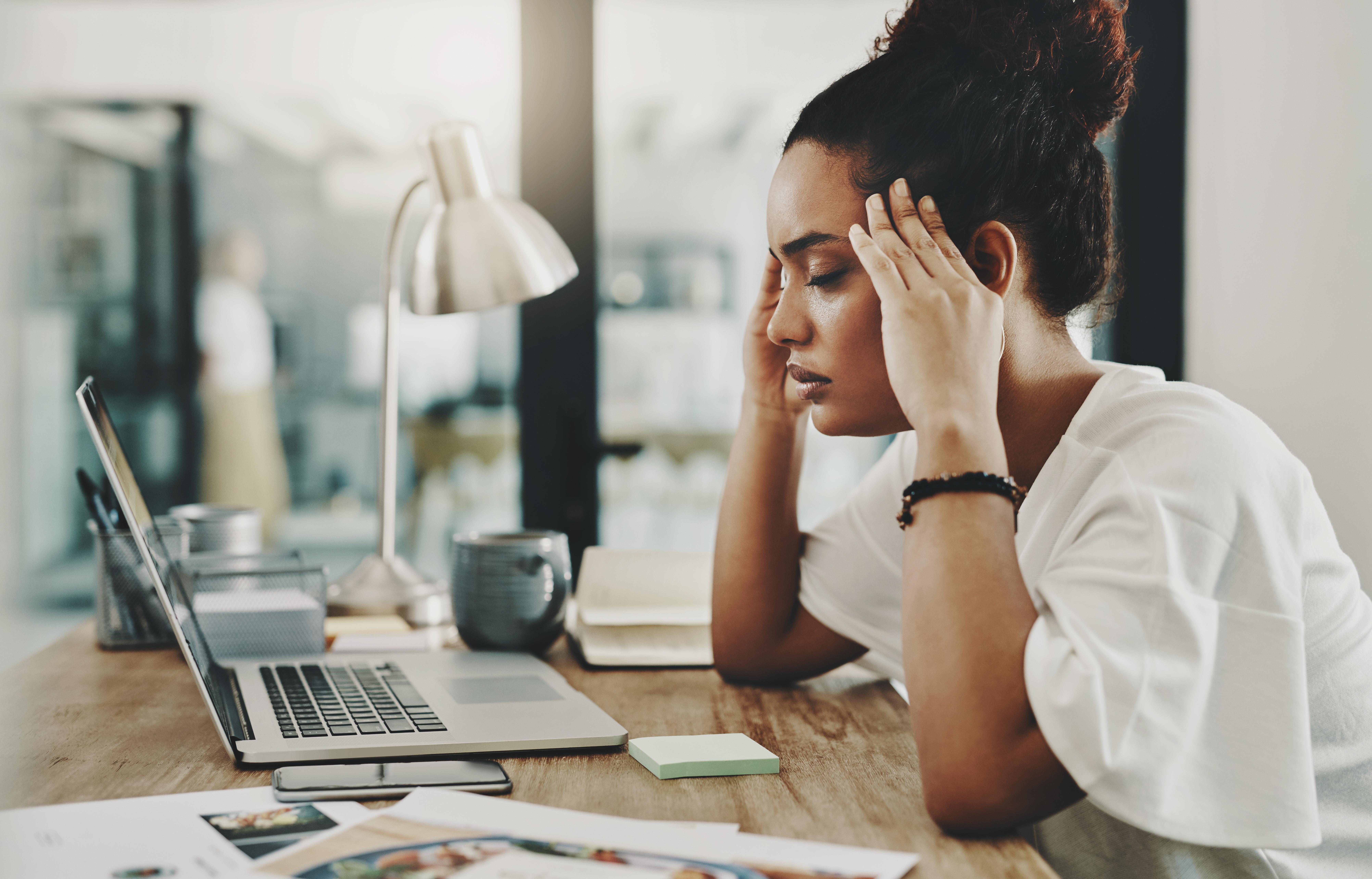 Stressaantuneena tietokoneen ääressä istuva nainen. Stressi vaikuttaa lantionpohjaan.