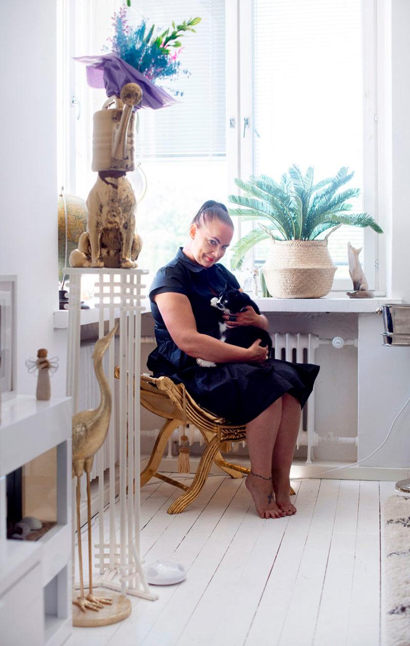 Satu-Maaria istuu kissa sylissään tuolilla.