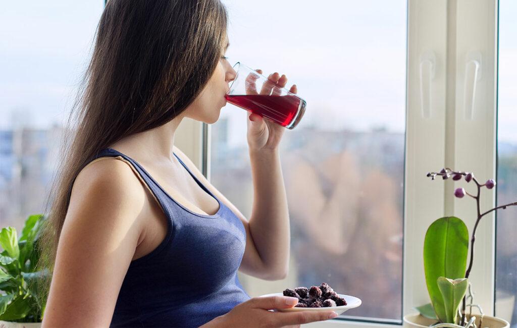 Nainen juomassa marjoista tehtyä mehua.