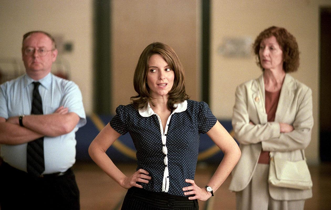 Tina seisoo kädet lantiollaan naisen ja miehen välissä.