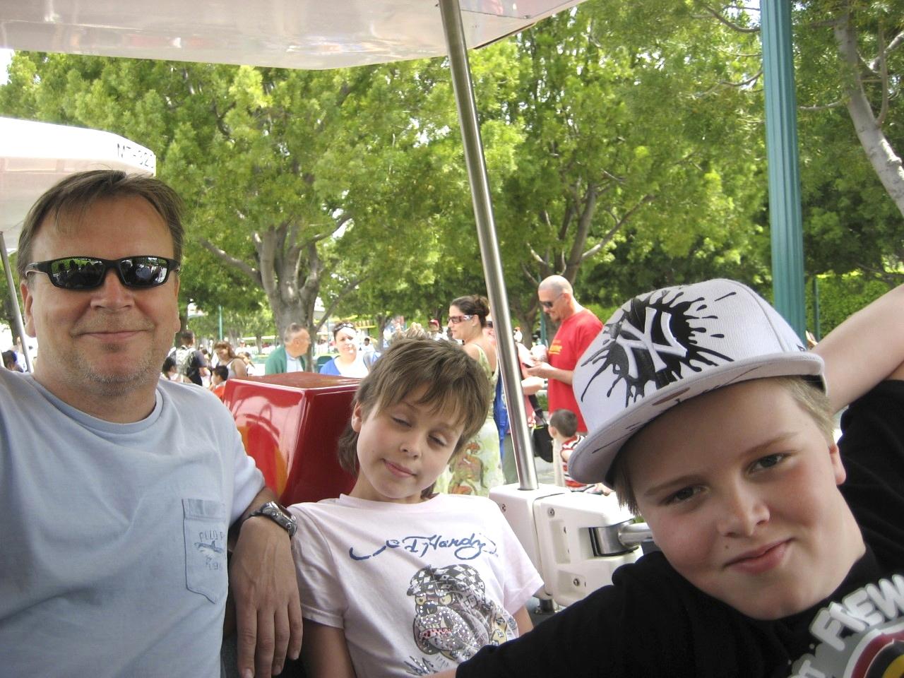 Jari Komulainen aurinkolasit silmillään, vieressä Alex ja Oskar.