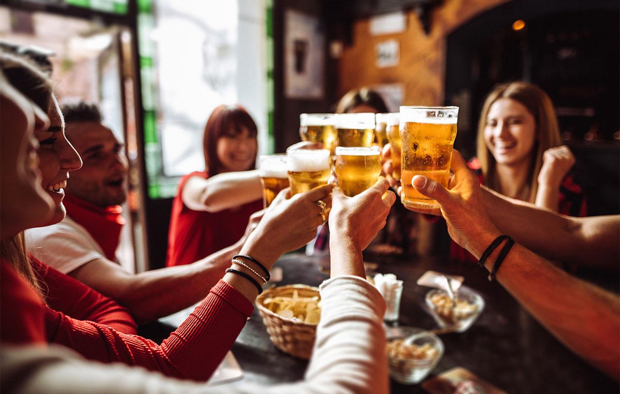 Porukka ihmisiä skoolaamassa oluen kanssa.