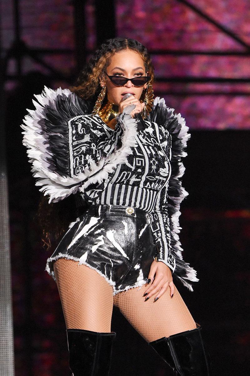 Beyoncé mustavalkoisessa esiintymisasussa, mikrofoni kädessään ja aurinkolasit nenällään niin, että hänen silmänsä näkyvät.