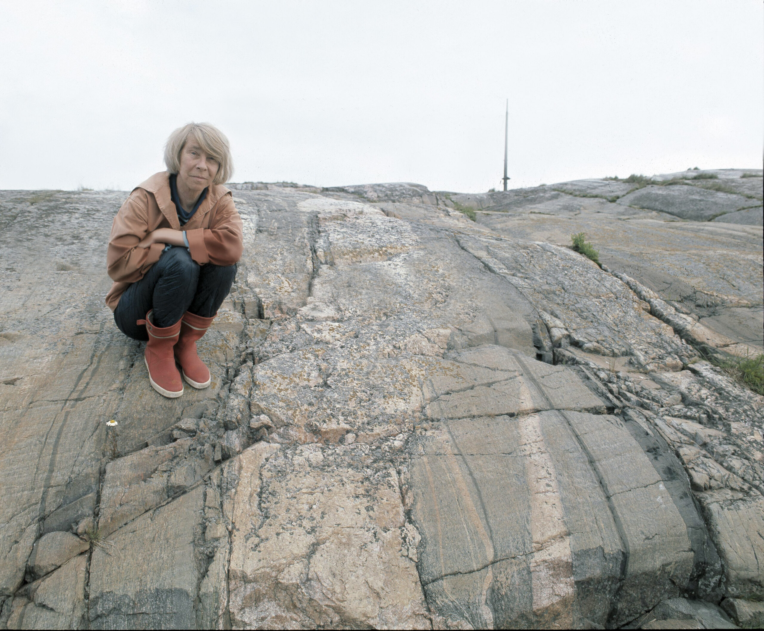 Tove Jansson kuvattuna ulkovaatteissa kalliolla 1970-luvulla.