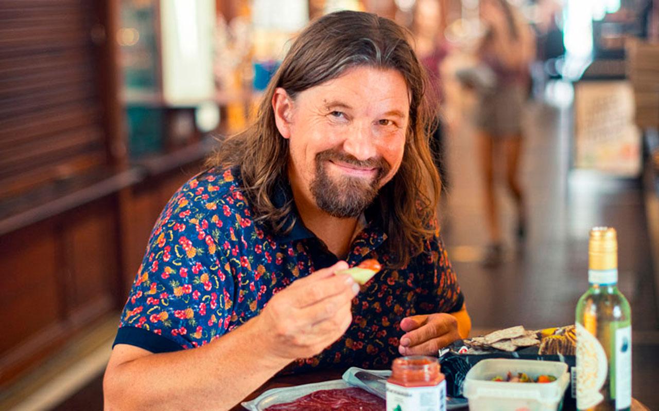 Kari Kanala istuu pöydän ääressä syömässä juustoja.