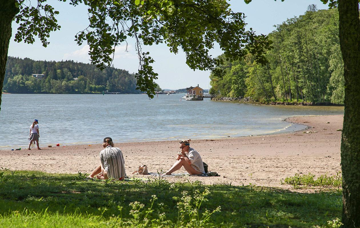 Ihmisiä rannalla, taustalla näkyy vettä.