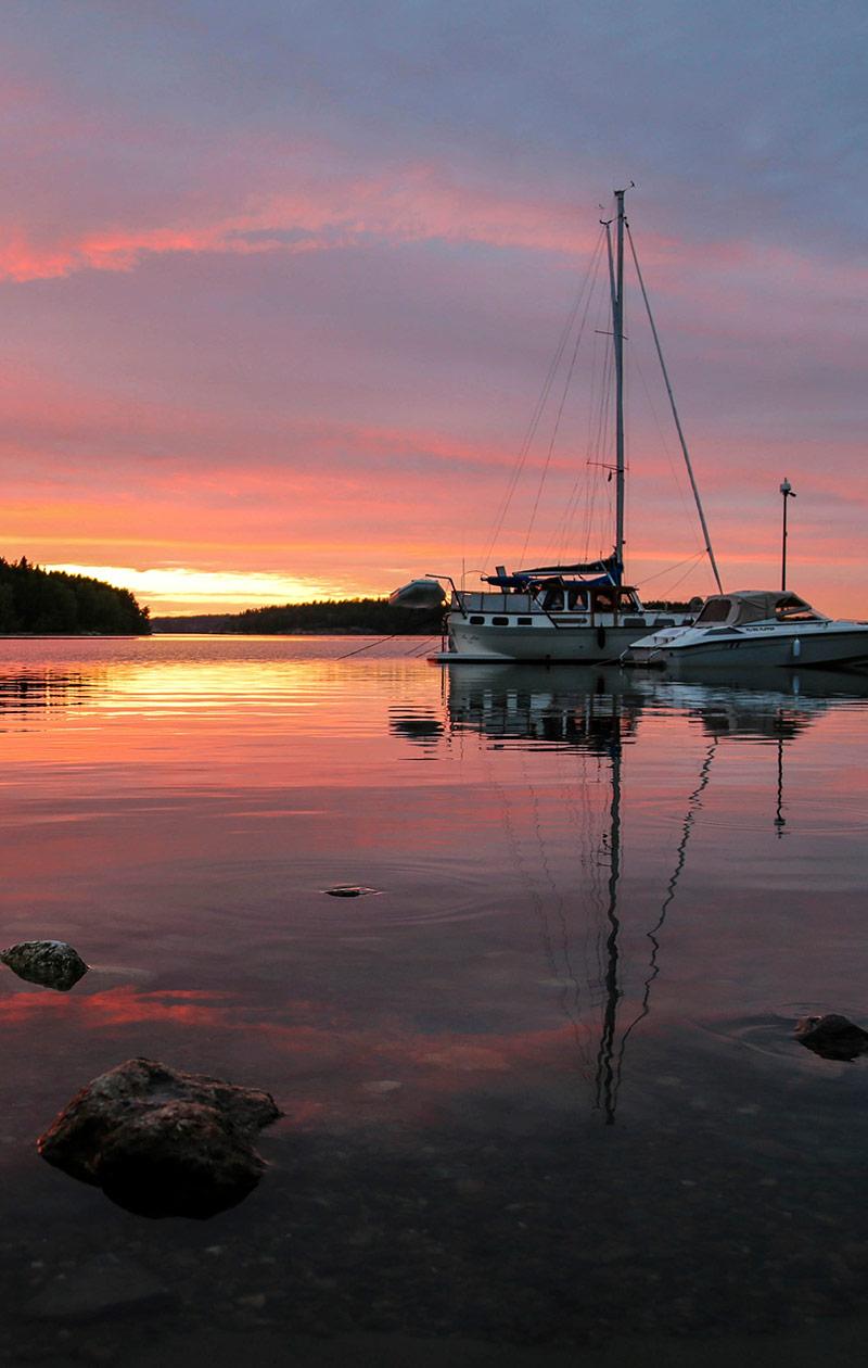 Meri ja veneitä auringonlaskussa.