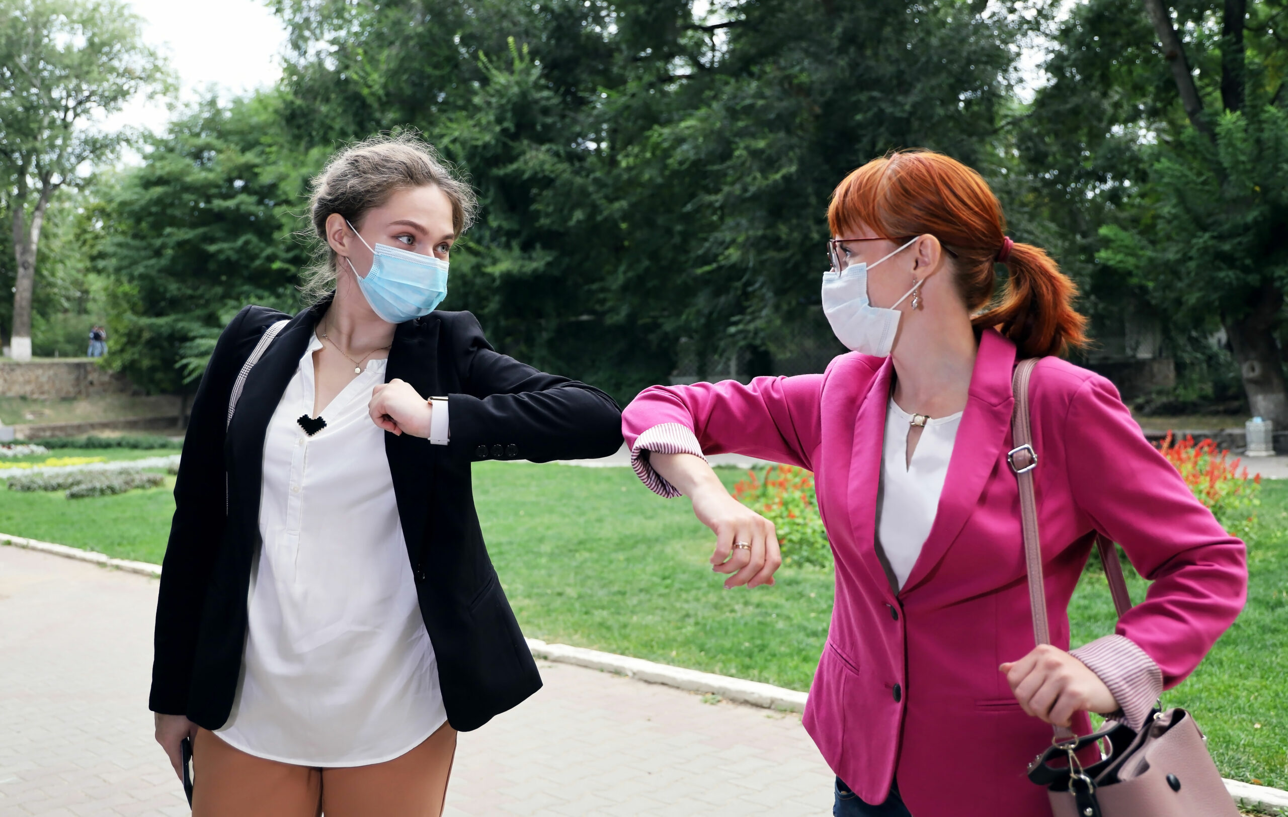 Kaksi naista kyynärpäätervehtii toisiaan maskit kasvoilla.