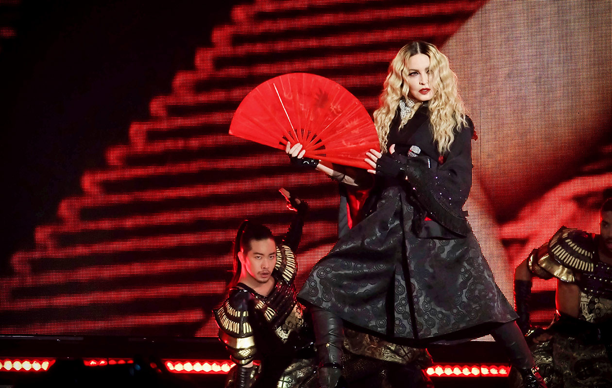 Madonna mustassa asussa punainen viuhka kädessään.