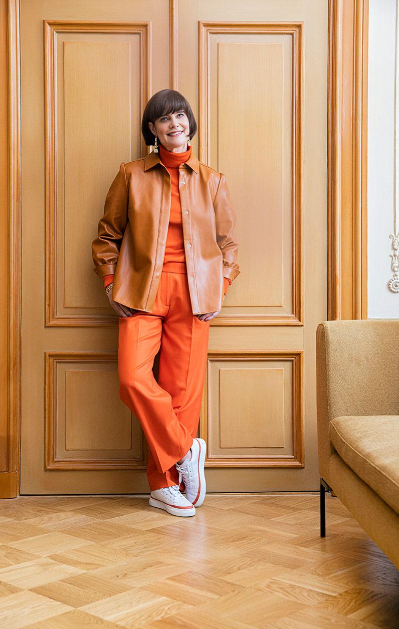 Oranssiin pukeutunut nainen.