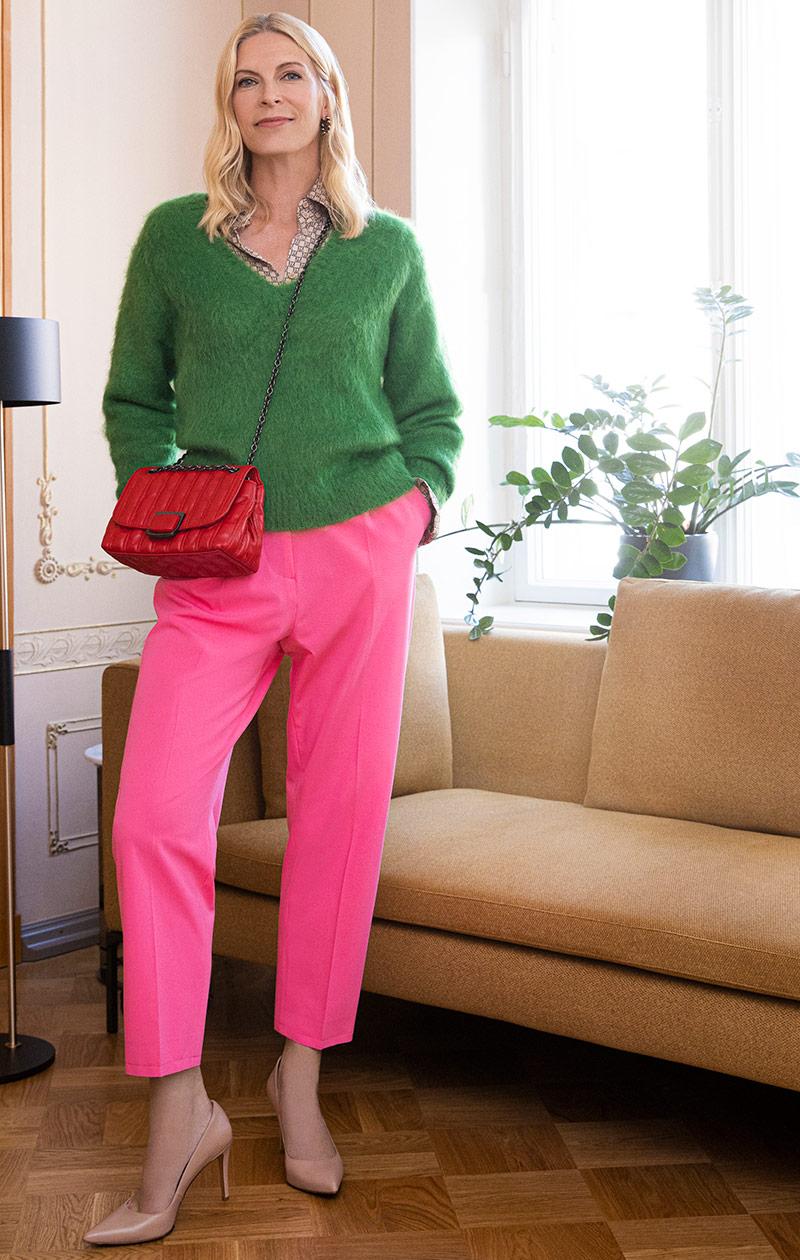 Vihreään neuleeseen ja pinkkeihin housuihin pukeutunut nainen.