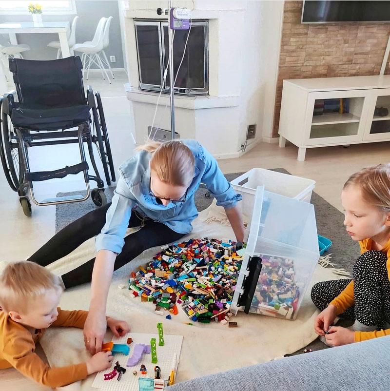 Sonja-Elina istuu olohuoneen lattialla ja rakentelee legoista lastensa Lennin ja Aadan kanssa.