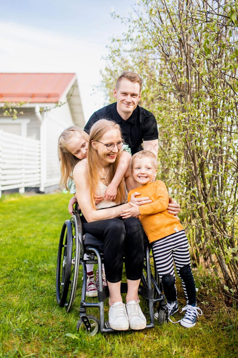 Sonja-Elina Tähtinen istuu pihalla pyörätuolissa ympärillään Jukka-puoliso ja lapset Aada ja Lenni.