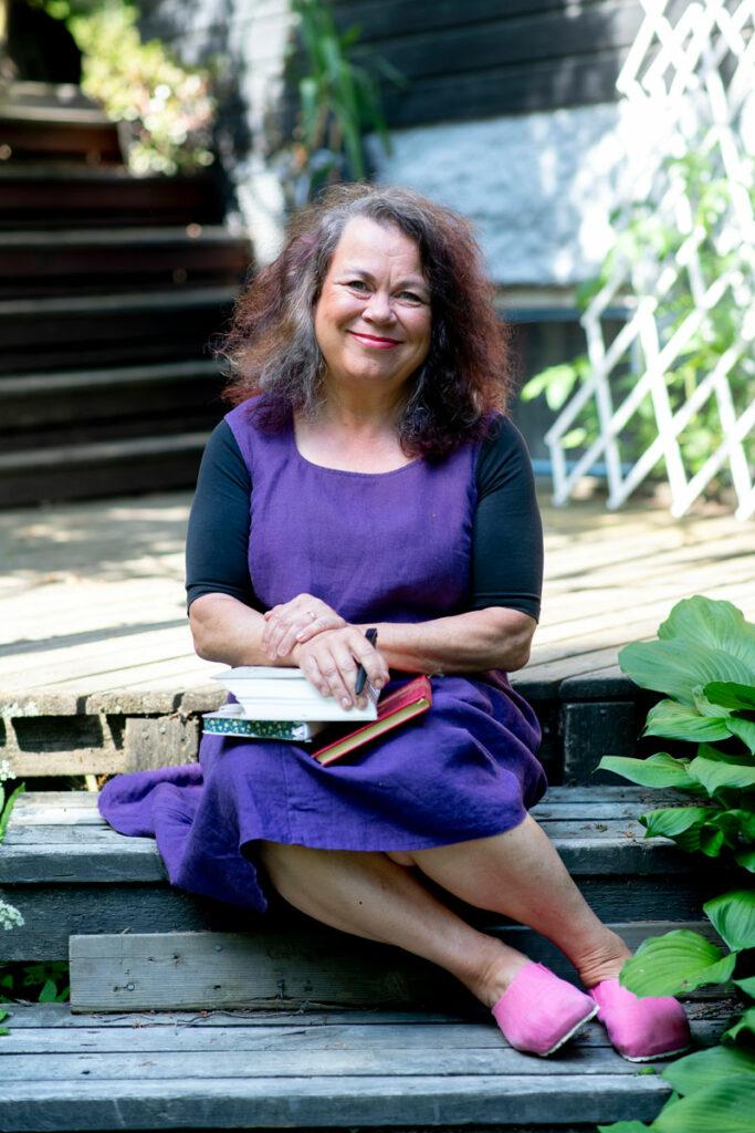 Kirjailija Leena Lehtolainen, 57, istuu portailla päiväkirjat sylissään.