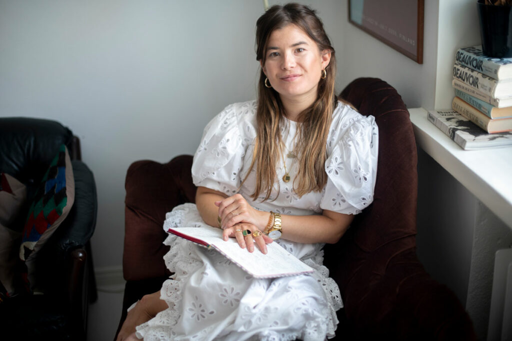 Kansallisteatterin näyttelijä Aksa Korttila, 30, istuu tuolissa päiväkirja sylissään.