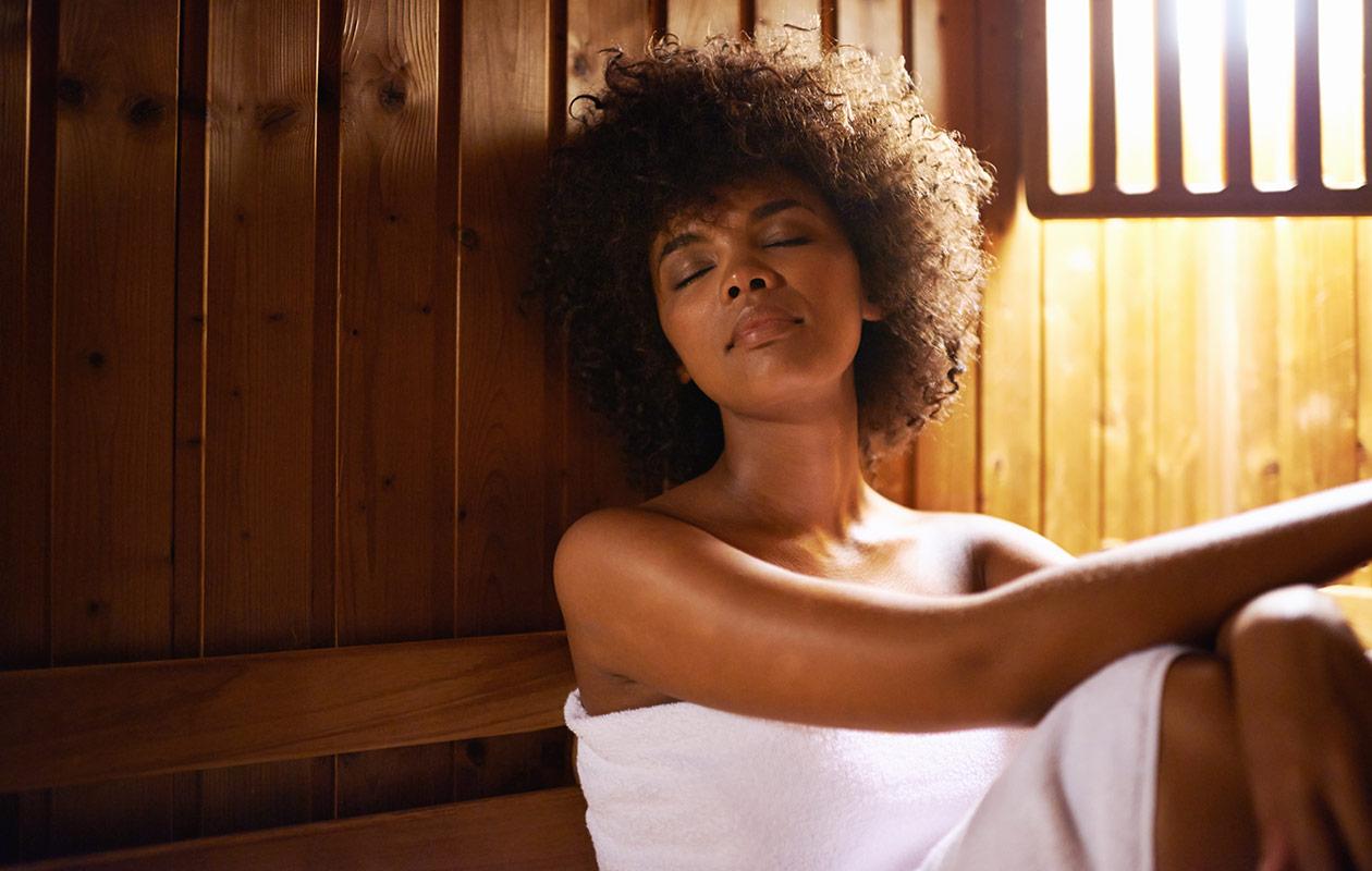 Saunakulttuuriin kuuluu saunaetiketti. Nainen rentoutuu lauteilla.