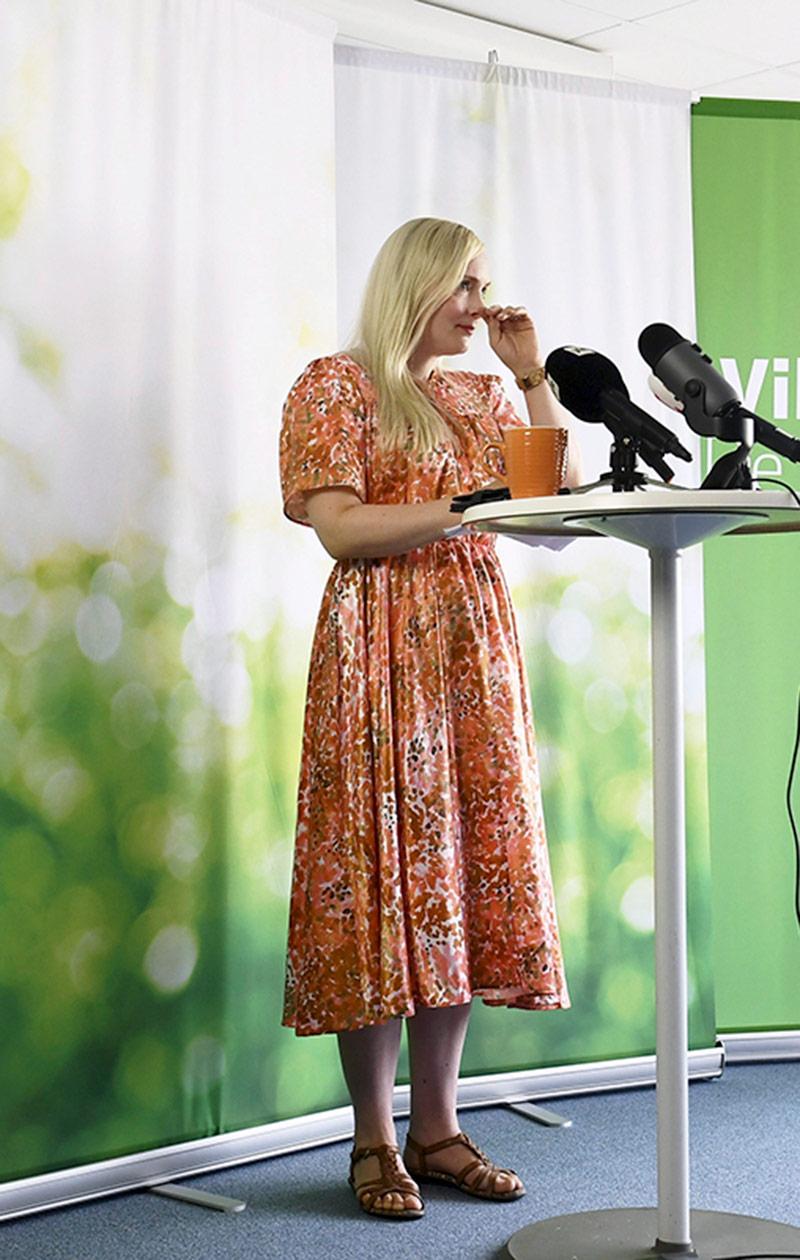 Maria seisoo pöydän ääressä, pöydällä on mikrofoneja.