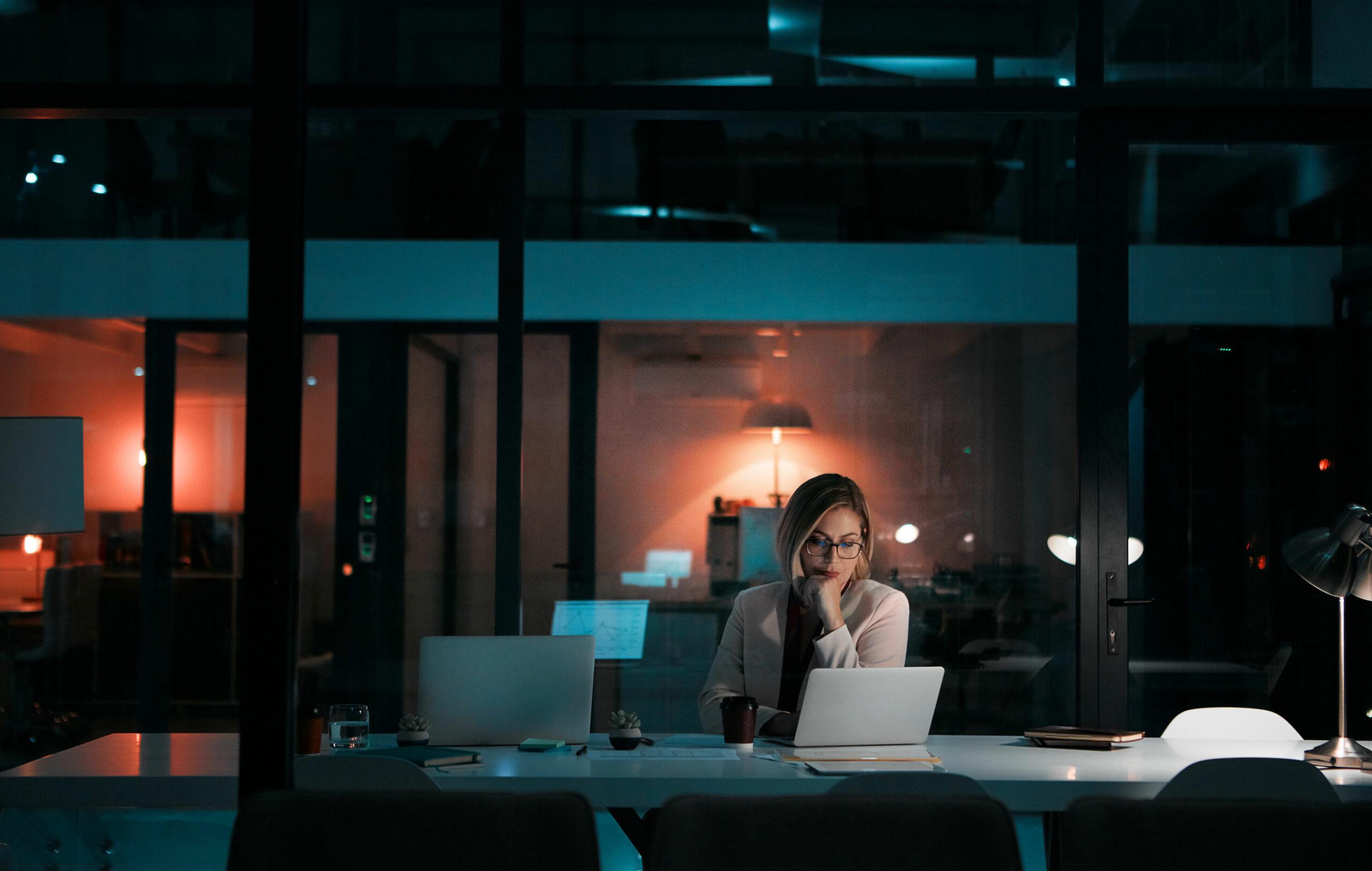Nainen työskentelee yksin muuten pimeällä toimistolla.