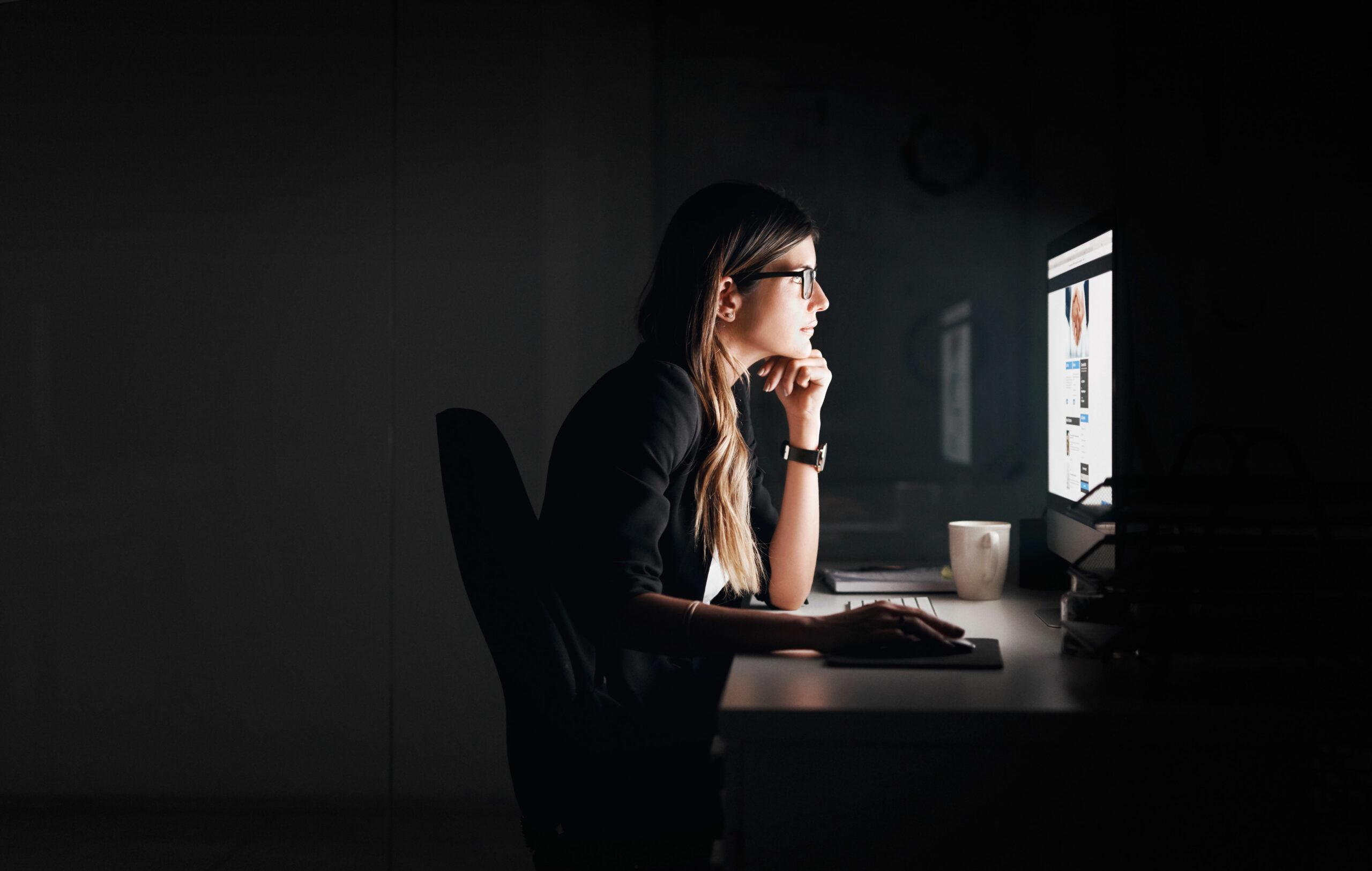 Nainen työskentelee tietokoneella muutoin pimeässä tilassa.