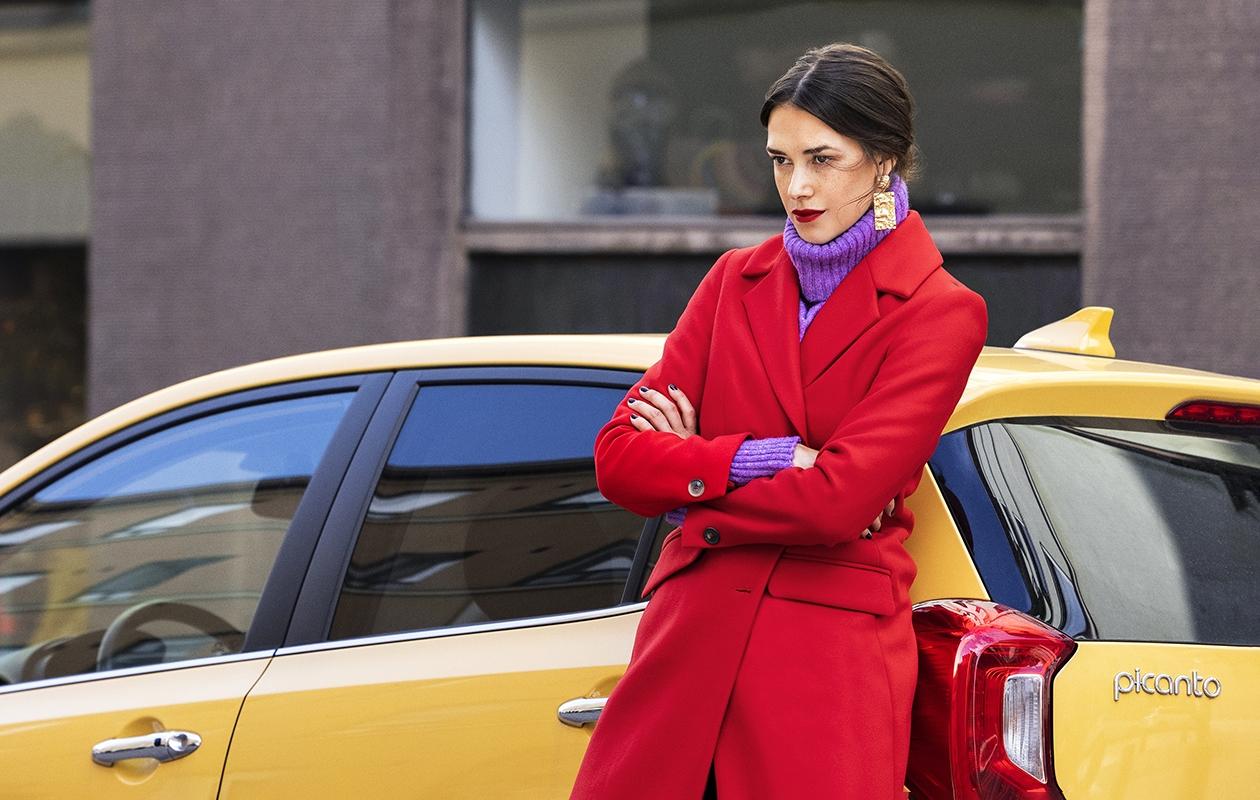 Nainen nojaa taksiin punainen villakangastakki yllään.