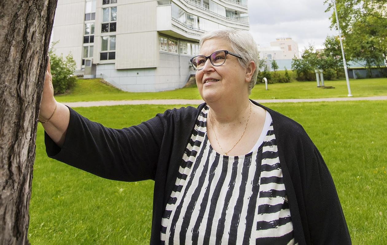 Eeva Nurminen nojaa puuhun kotipihallaan.