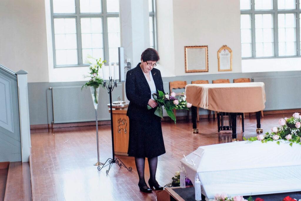 Eeva Nurminen hautajaisissa arkun äärellä.
