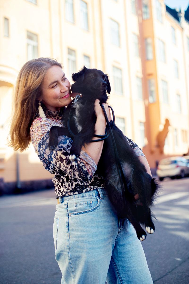 Annukka Karhu sylissään rescue-koira Lulu.