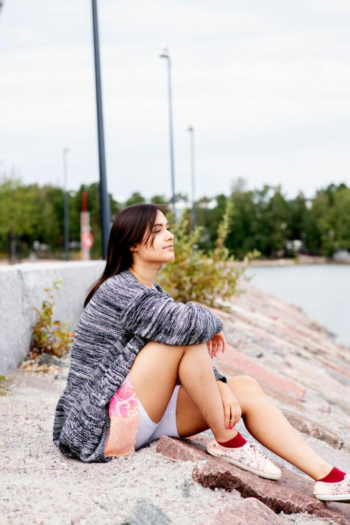 Liana Linvik istuu rantakalliolla Aurinkolahden uimarannalla Helsingissä.