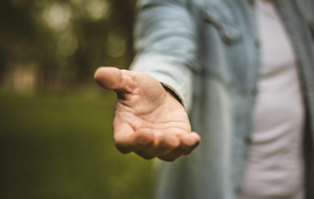 Ihminen ojentaa kätensä kohti katsojaa.