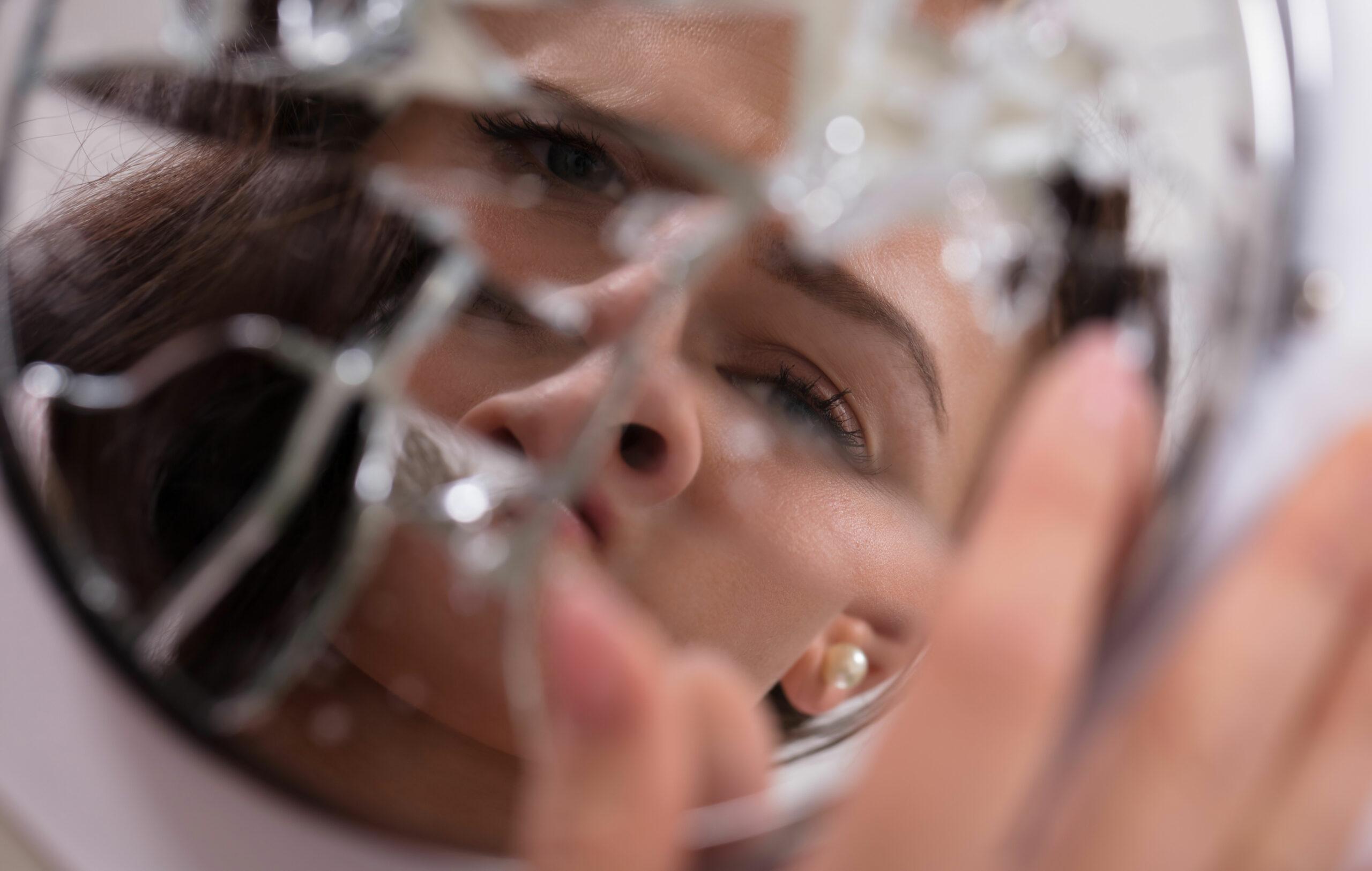 Dysmorfinen ruumiinkuvan häiriö – ihminen katsoo kasvojaan rikotusta peilistä.