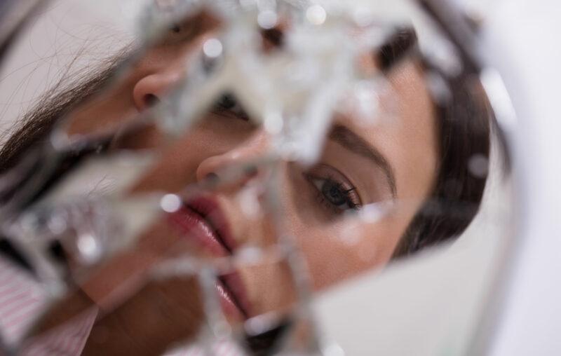 Rikkoutunut peili, josta heijastuvat kasvot