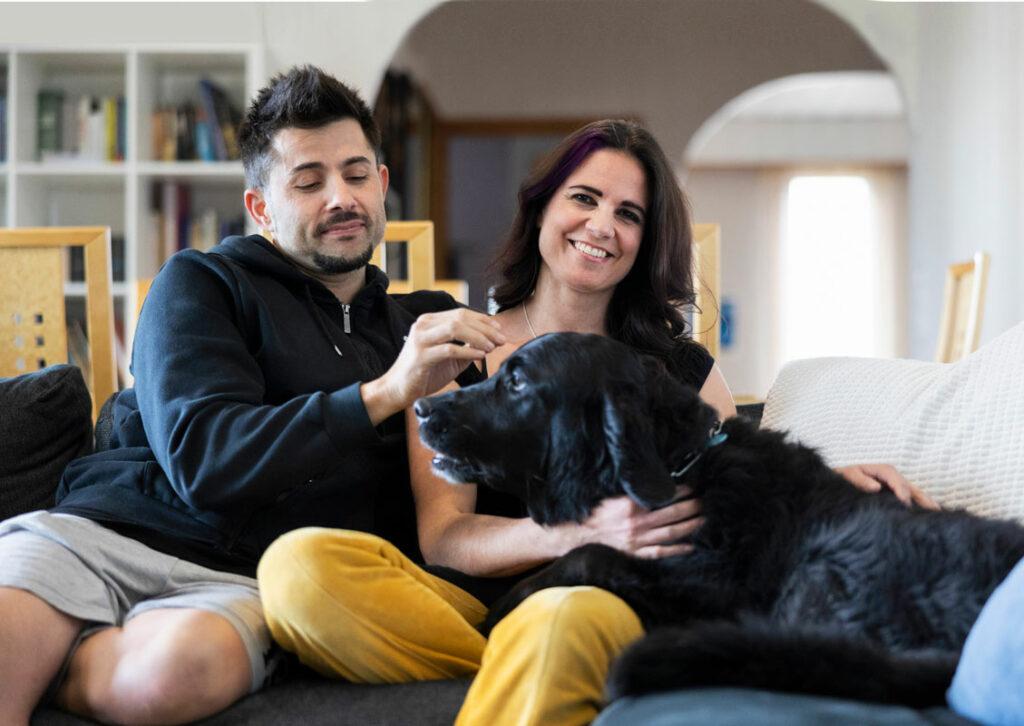Salima Peippo, hänen miehensä Christian Fernandez ja perheen Max-koira kotisohvallaan.