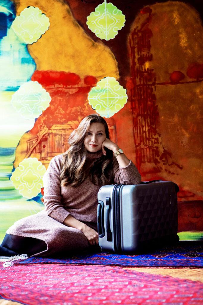 Nelli Mikkola matkalaukkunsa kanssa lapsuudenkodissaan Pornaisissa. Taustalla oleva maalaus on hänen äitinsä Irmeli Mäkilän.
