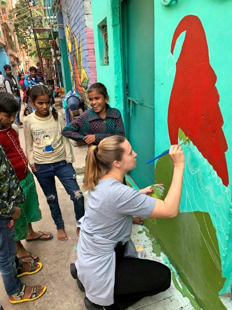 Nelli Mikkola maalaa talon seinää slummilasten kanssa New Delhissä.