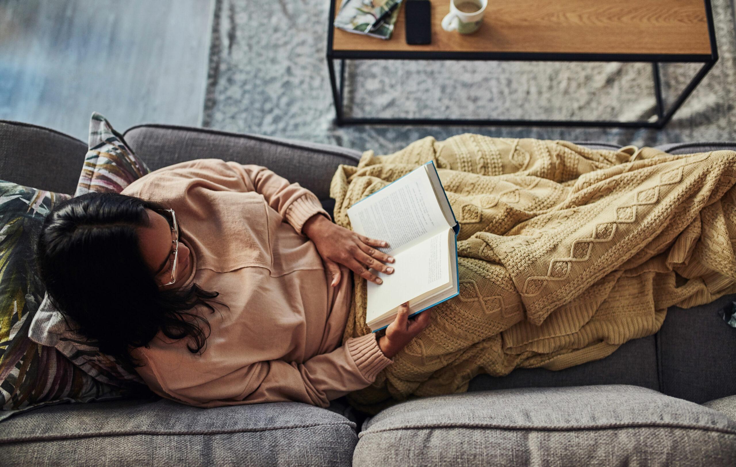 Kirjasarjan lueskelua sohvalla viltin alla maaten.
